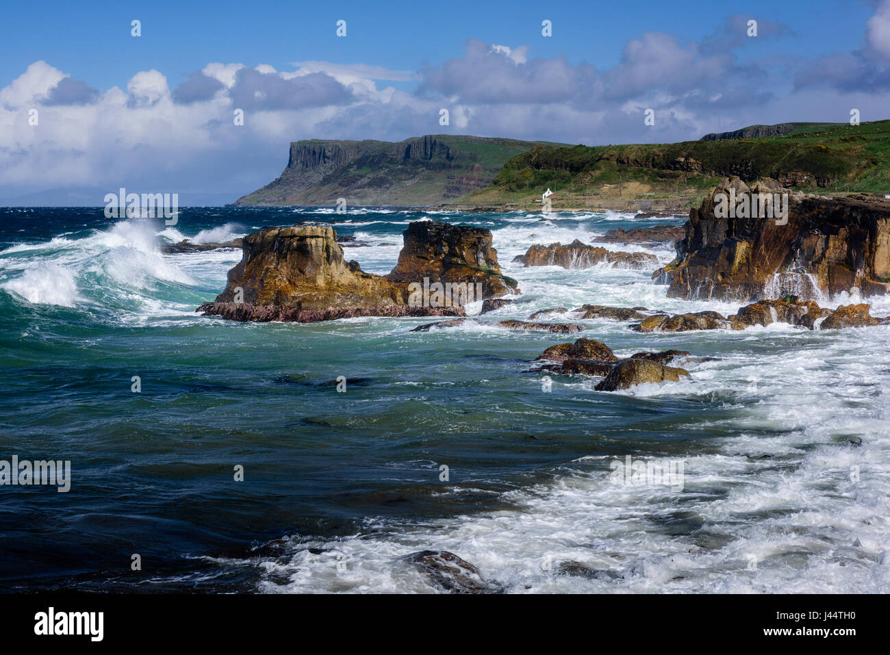 Rocky shoreline at Ballycastle on the Causeway coast of County Antrim in Northern Ireland looking east towards Fair - Stock Image
