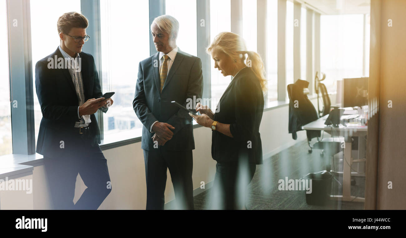 Three business people standing together in office with mobile phone and digital tablet. Corporate professional having - Stock Image
