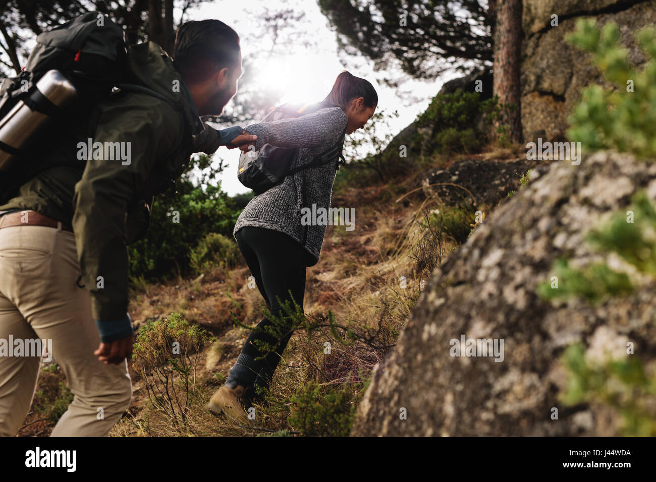 Female hiker helping her boyfriend uphill in the countryside. Young couple hiking in mountain. - Stock Image