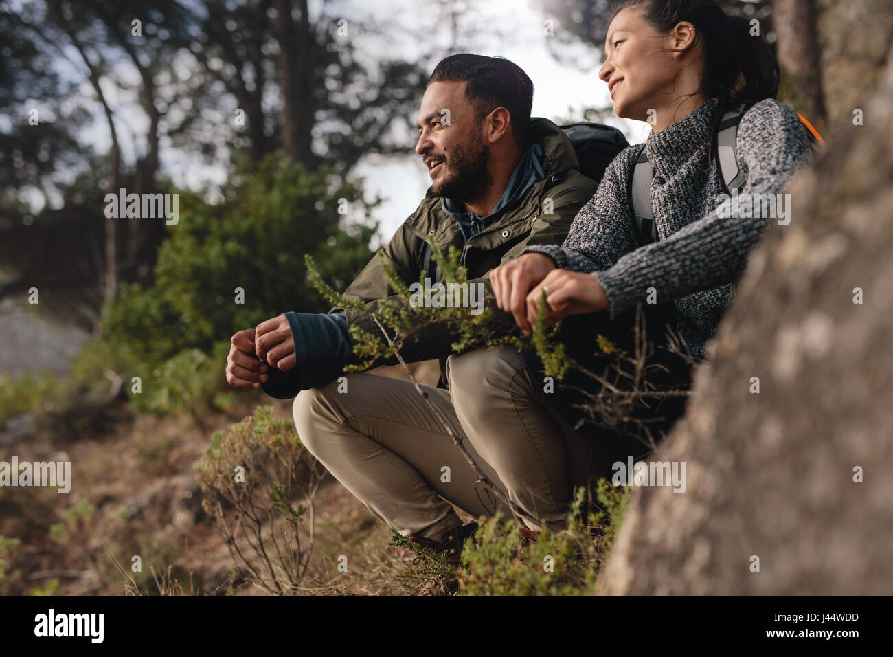 Couple taking a break after hiking uphill in the countryside. Young man and woman sitting on mountain and looking - Stock Image