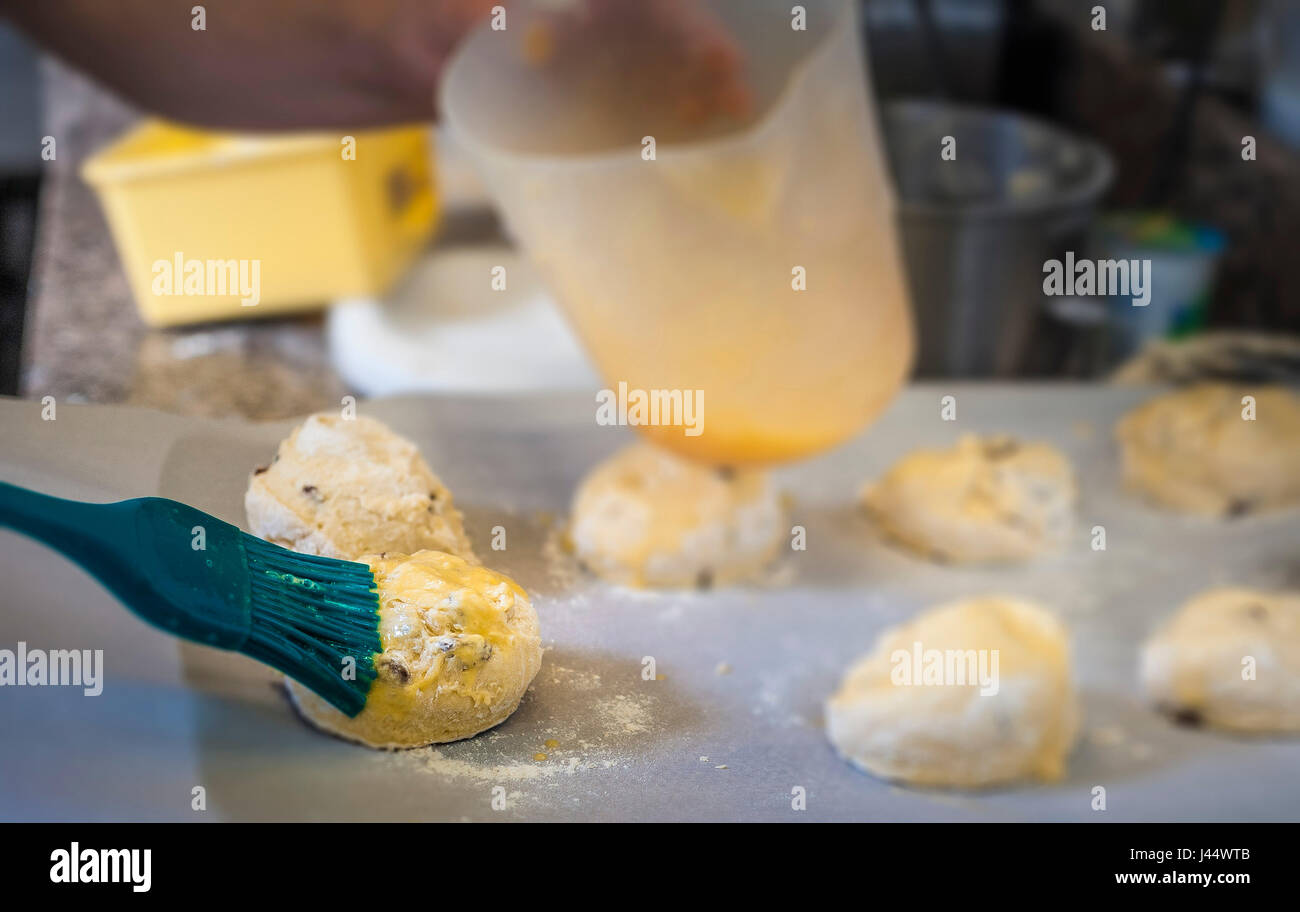 A chef applies an egg wash to scone dough Kitchen Food Cooking Baking Restaurant Food preparation Food service industry - Stock Image