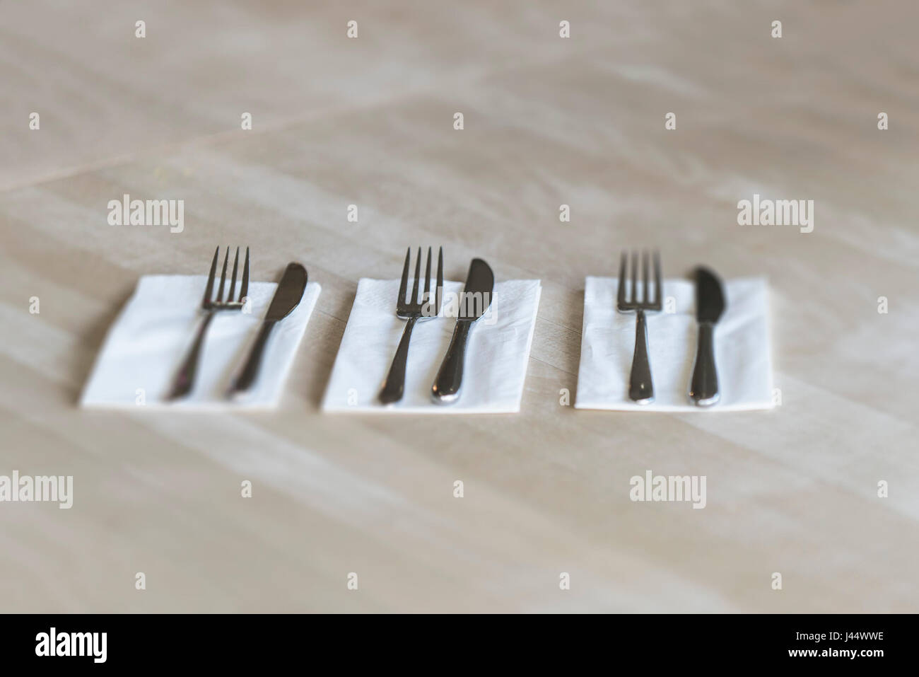 Cutlery on a table in a restaurant Knives Forks Napkins Serviettes Clean Unused Utensils - Stock Image