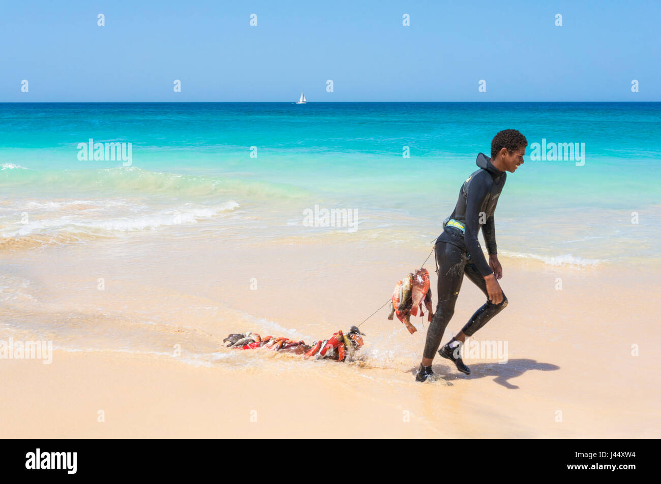 CAPE VERDE SAL young boy in wetsuit on Ponta Preta beach near  draging a catch of fishing on a line behind, santa Stock Photo