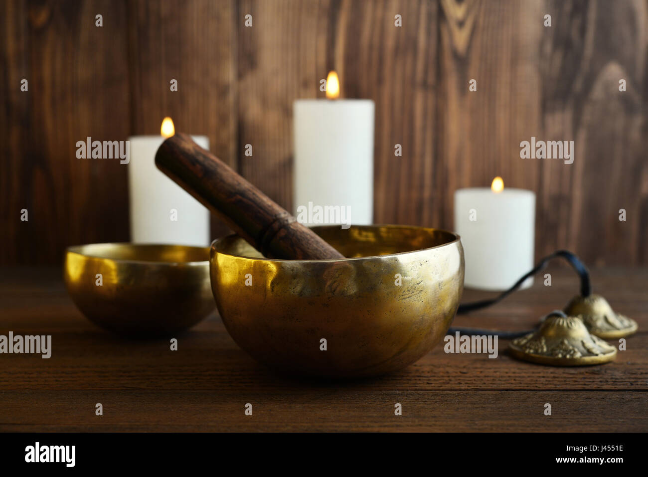 Tibetan handcrafted singing bowls with sticks on wooden background - Stock Image