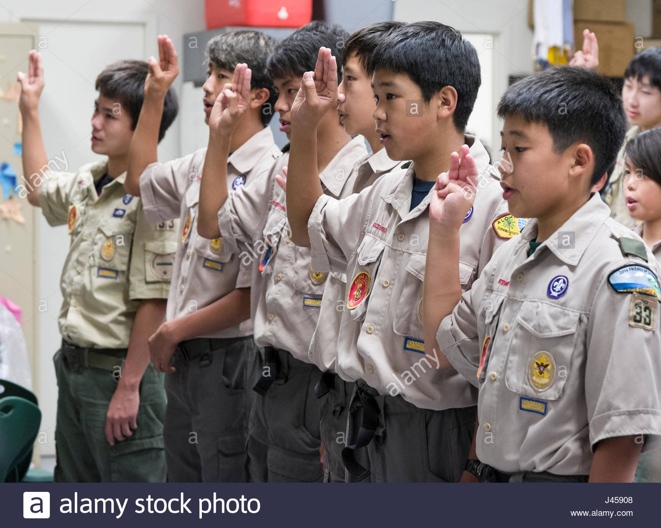 Group of Boy Scouts standing at attention making the Boy Scout sign with their hand, Honolulu, Oahu, Hawaii, USA - Stock Image