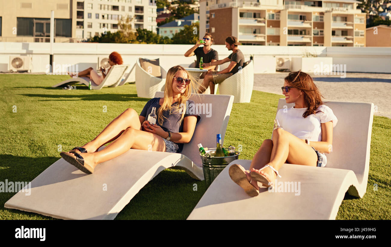 Two girls relaxing while laying on sunbeds in the sun Stock Photo