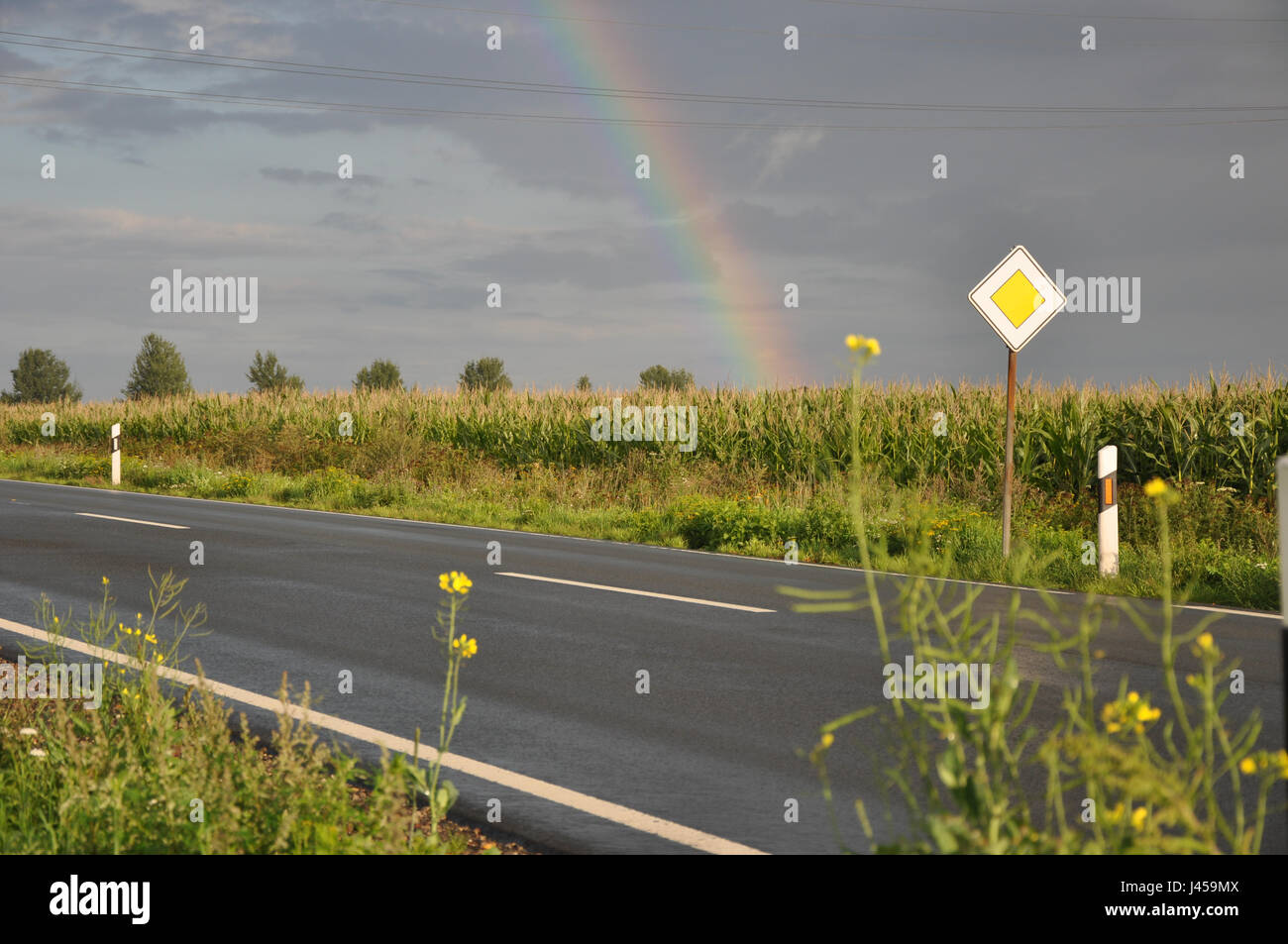 Regenbogen über einer Landstrasse in Niedersachen, in der Nähe von Nienburg. - Stock Image