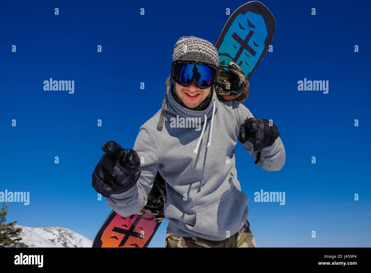 Successful young man snowboarding in the mountains Sheregesh. Snowboarder resting on mountain top. Caucasian snowboarder - Stock Image