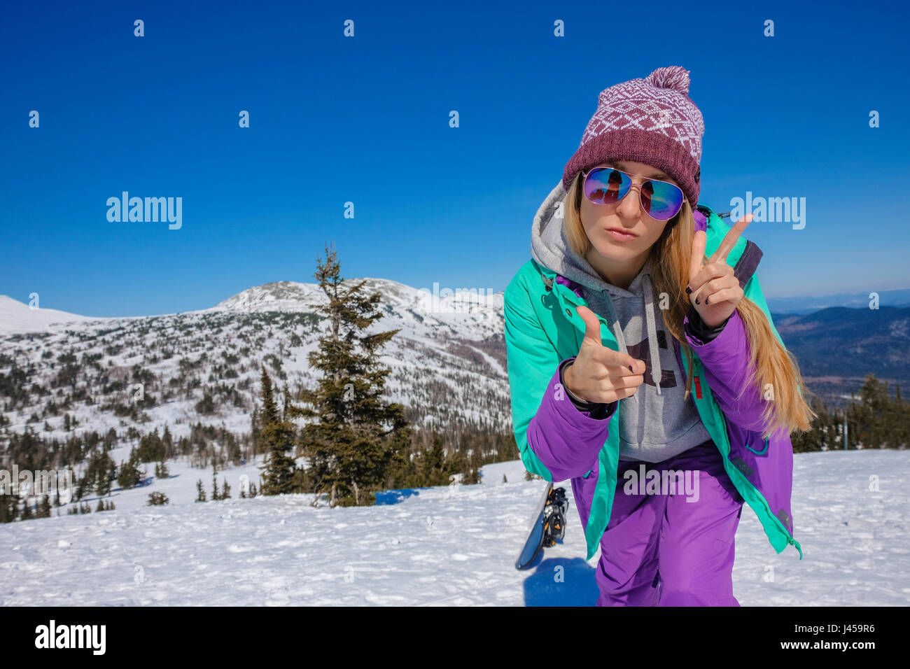 Successful young girl snowboarding in the mountains Sheregesh. Snowboarder resting.  Stylish caucasian snowboarder.Snowboarder - Stock Image