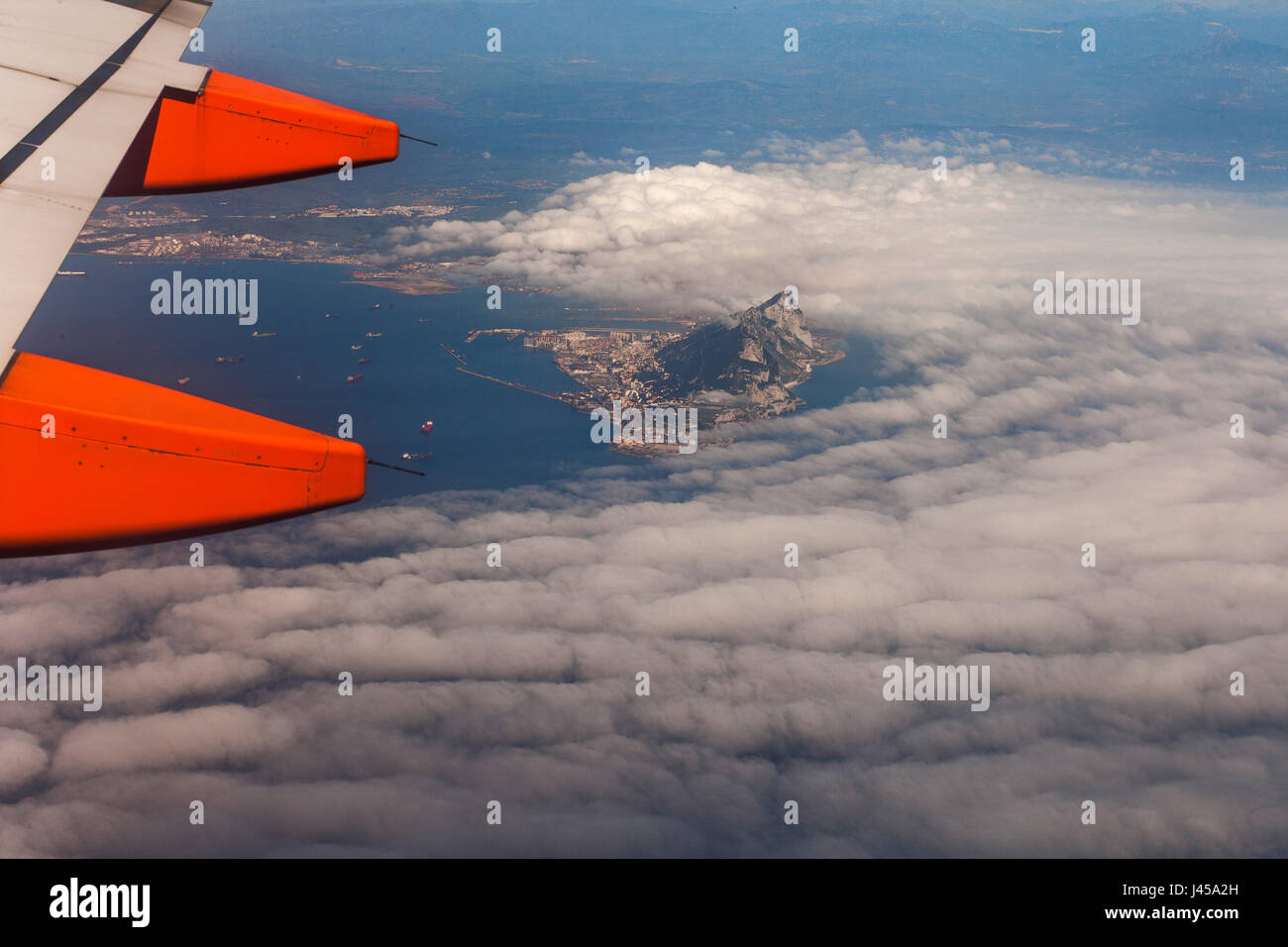 An aerial view of the rock of Gibraltar poking out from low flying clouds as seen from an Easy Jet aeroplane window - Stock Image