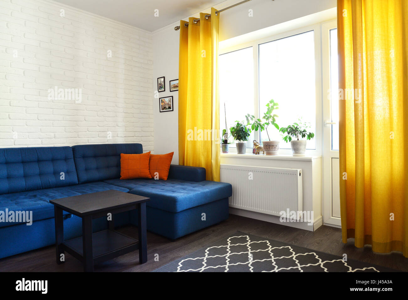 Clean Family Room With Blue Couch, White Brick Wall And Yellow Curtains.  Design Interior Concept.