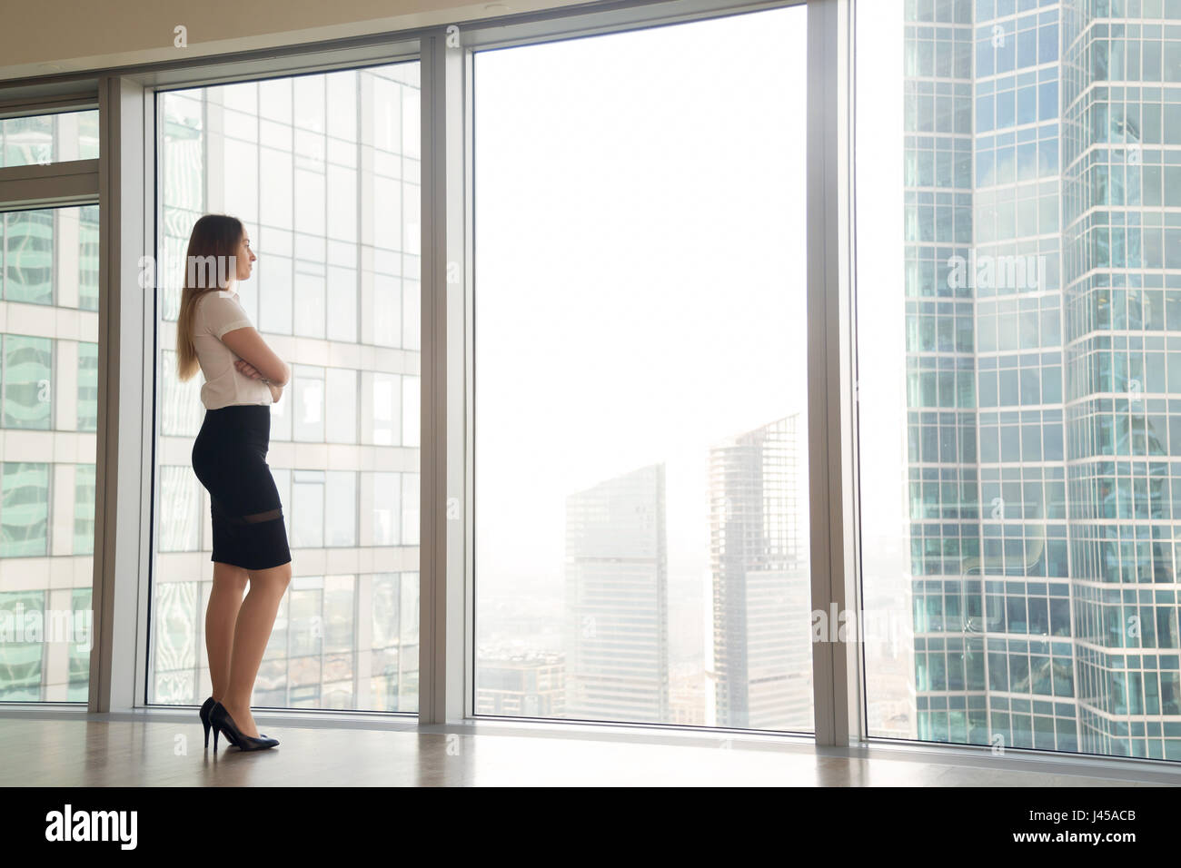 Woman thinking about plans on future near window Stock Photo