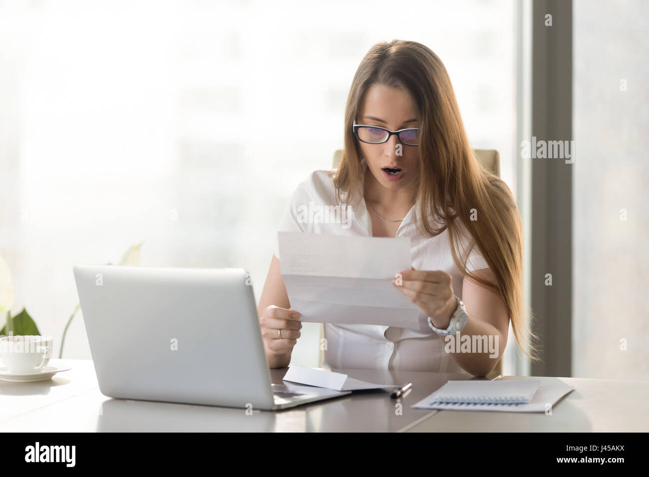 Female entrepreneur holds notice about loan debt - Stock Image