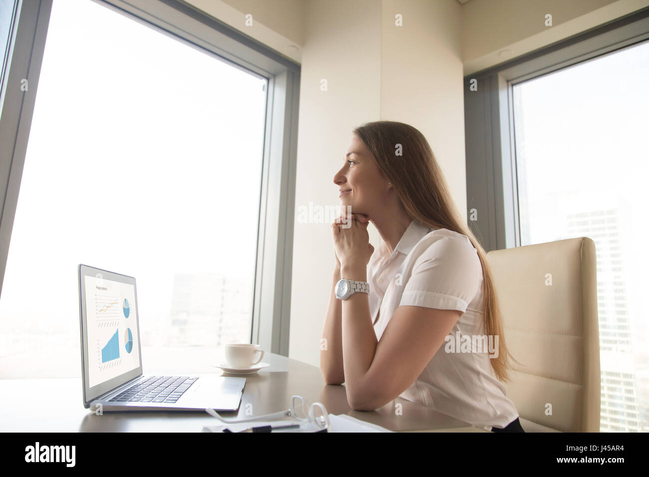 Businesswoman dreamily ponders about future - Stock Image