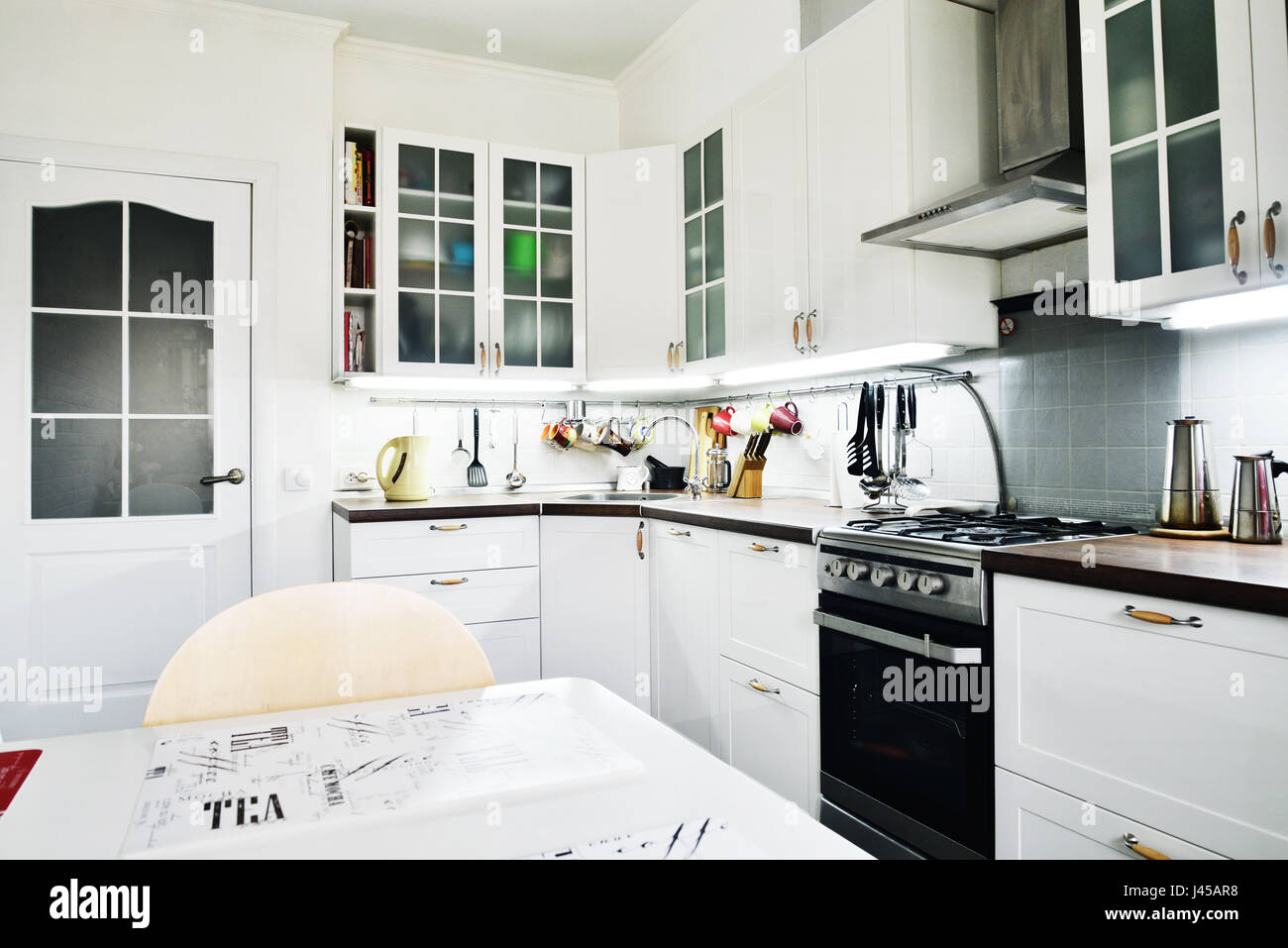 Interior of the kitchen in Scandinavian style with white furniture and a dining table Stock Photo