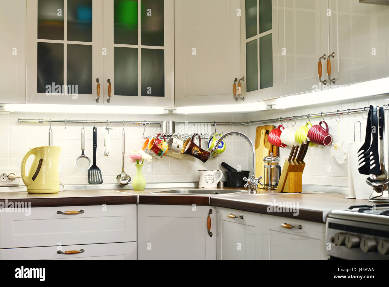 A fragment of the Scandinavian style kitchen with rail system and kitchen utensils - Stock Image