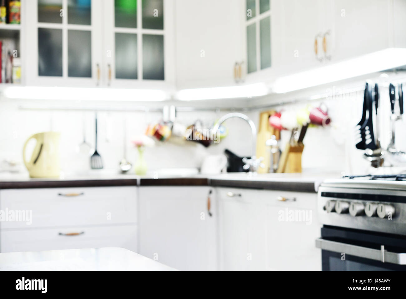 Blurred background. Modern kitchen with railings system  and kitchen utensils. - Stock Image