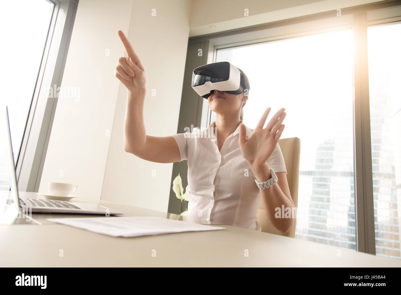 Business woman wearing virtual reality glasses - Stock Image