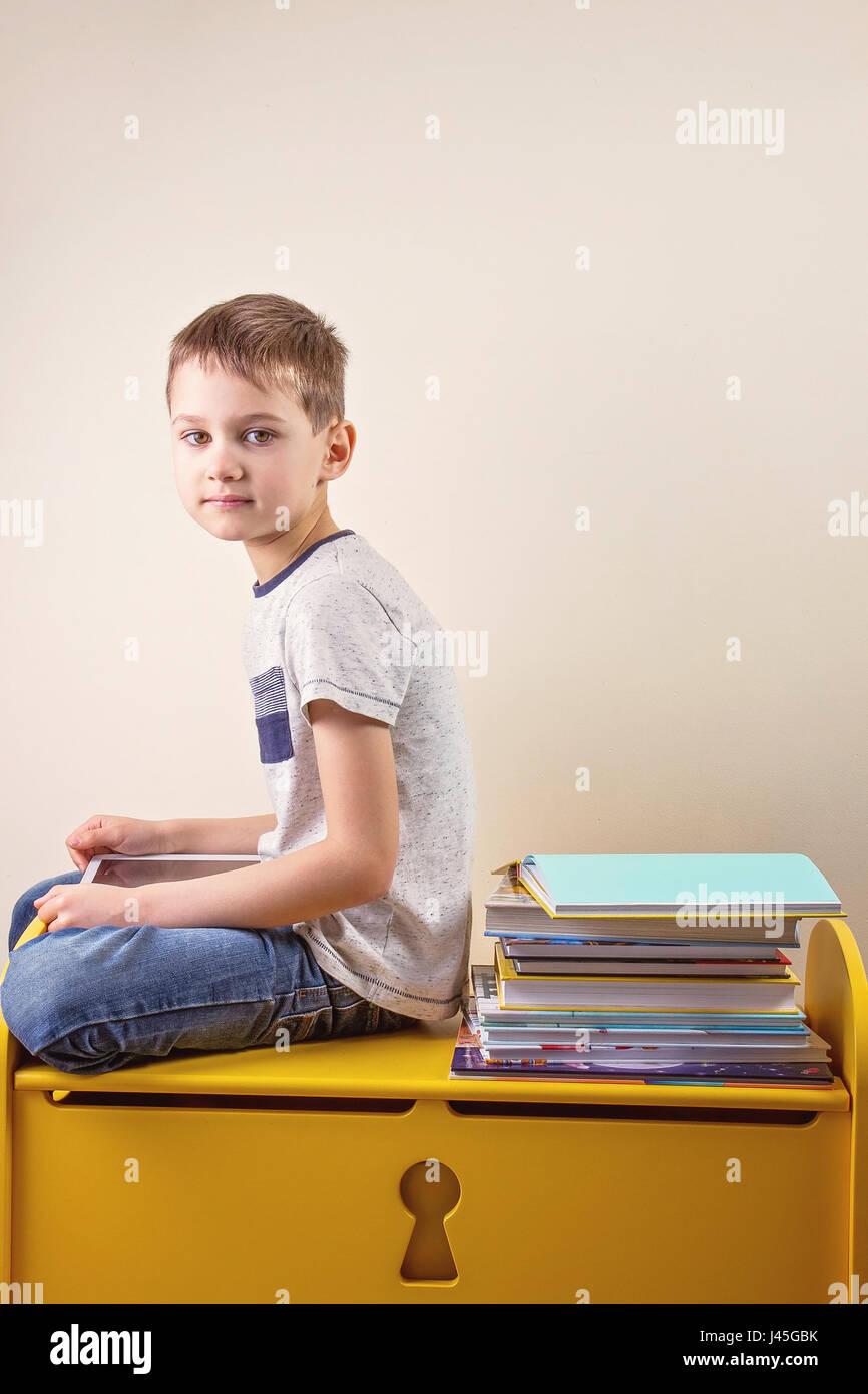 Kid using digital tablet sitting near bis stack of books - Stock Image