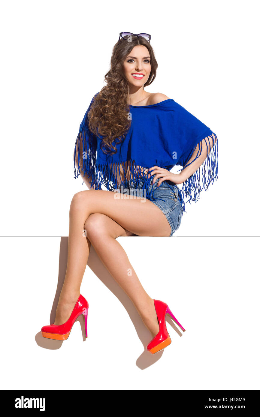 Beautiful young woman in blue top, jeans shorts and high heels sitting with legs crossed on the top of white banner - Stock Image