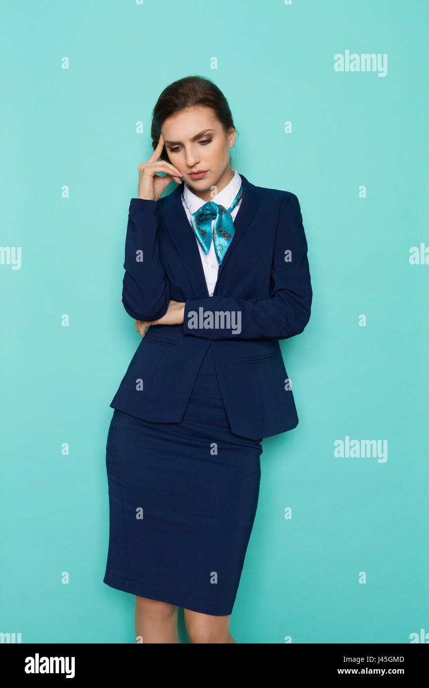Sad young businesswoman in blue suit and turquoise scarf is looking down and thinking. Three quarter length studio - Stock Image