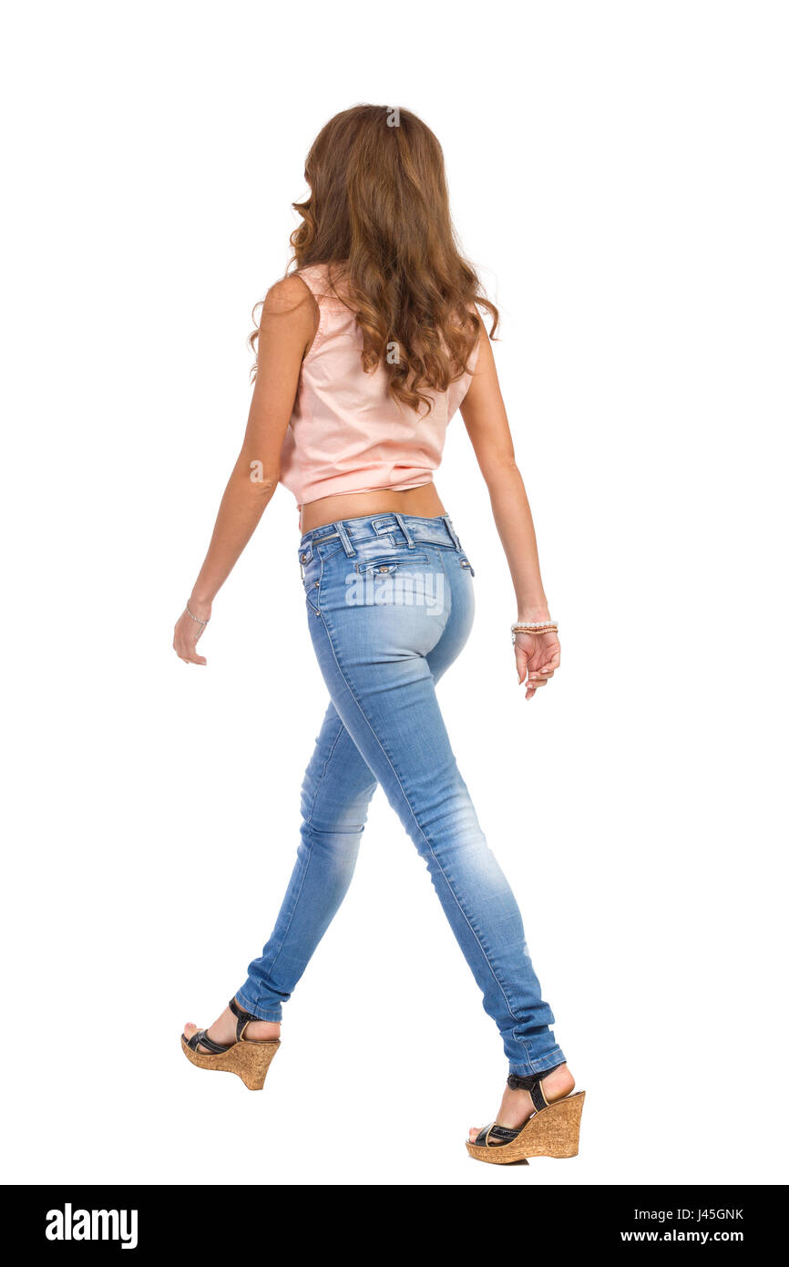 Woman in pink shirt, jeans cork heels walking. Rear side view. Full length studio shot isolated on white. - Stock Image