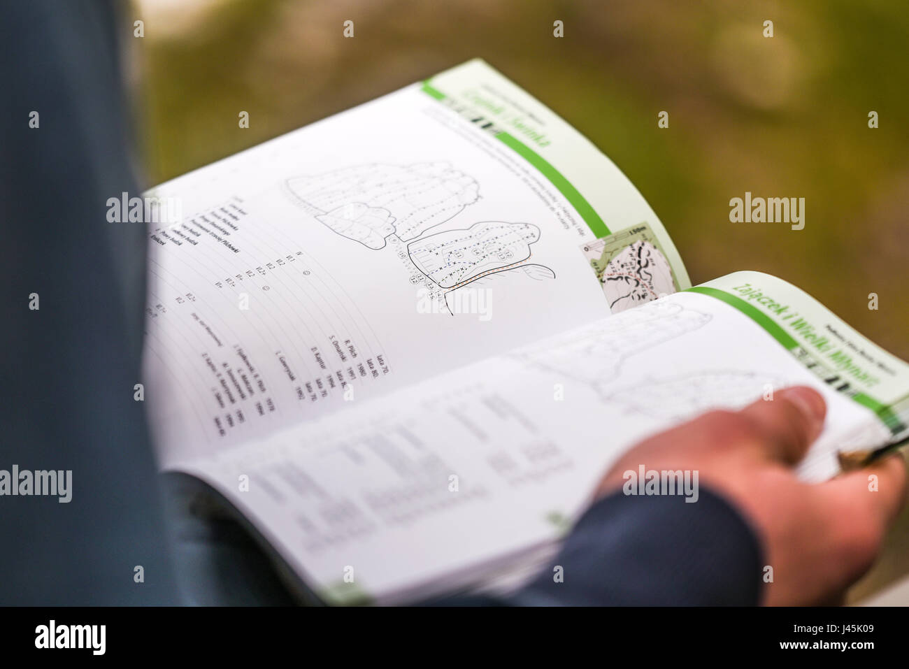 Climber holdin a topo book in his hands. - Stock Image