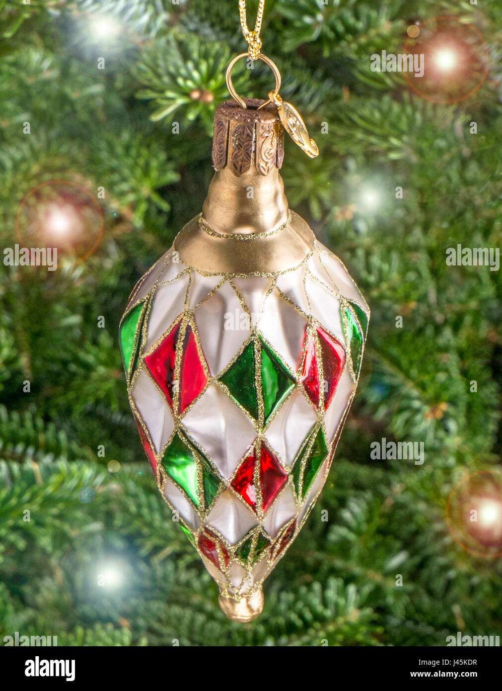 Christmas bauble hanging from a tree in the shape of a Harlequin Jewel - Stock Image