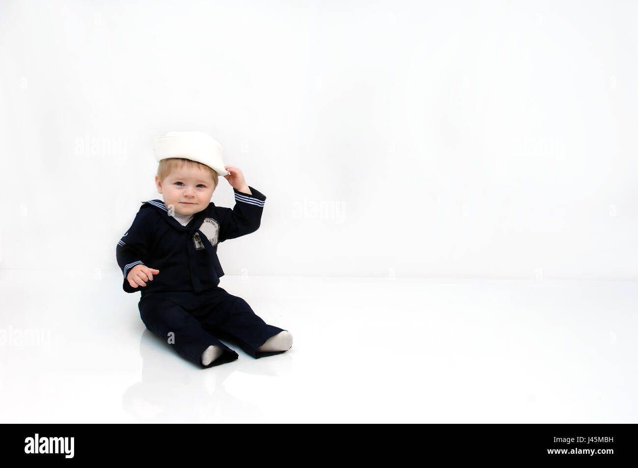 02f4ea2f4 Baby boy is wearing a navy, sailor costume. He is smiling and Stock ...