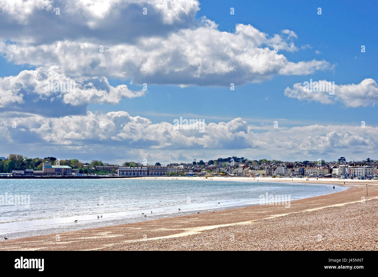 Weymouth beach -Dorset panoramic view  sweeping vista of seafront - attractive town beyond - early summer sunlight - Stock Image