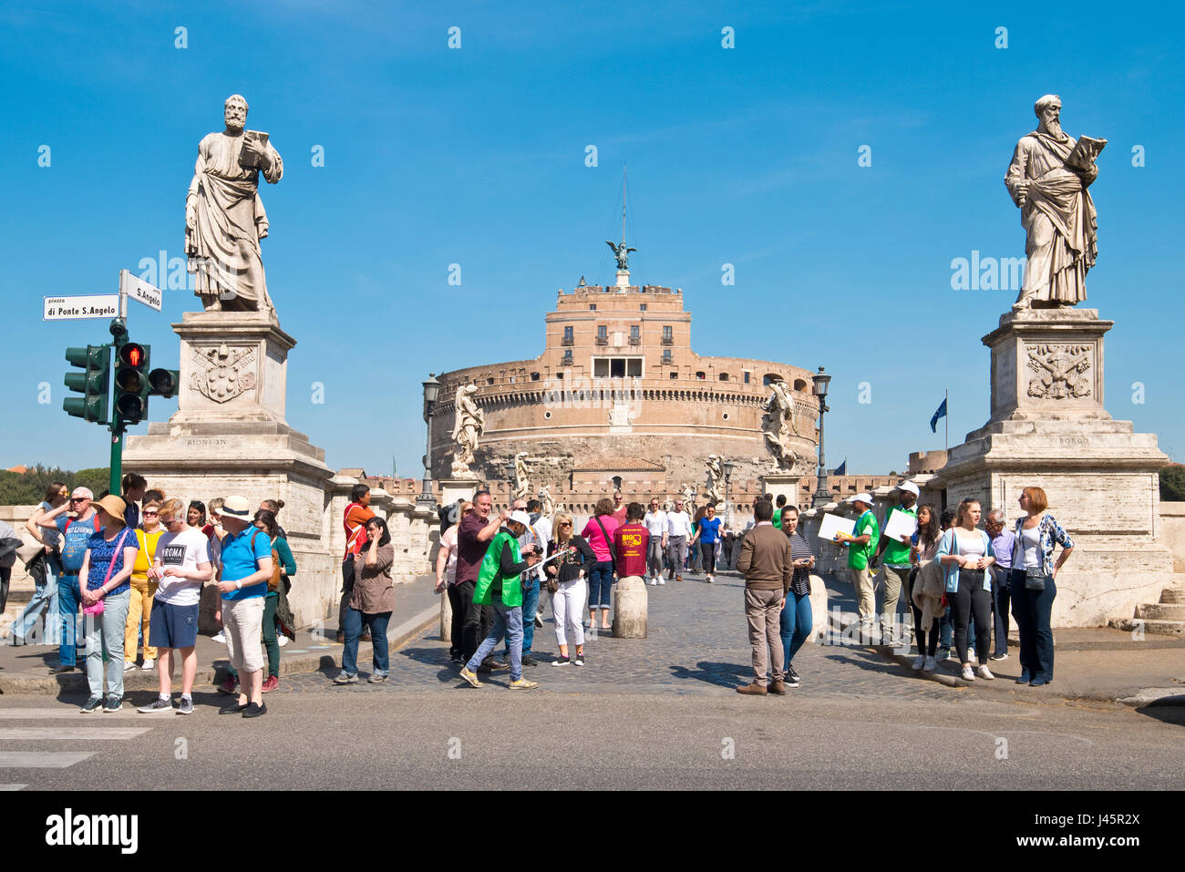 The Castel Sant'Angelo with the tourists walking across the pedestrian St. Angelo Bridge or Ponte Sant'Angelo - Stock Image