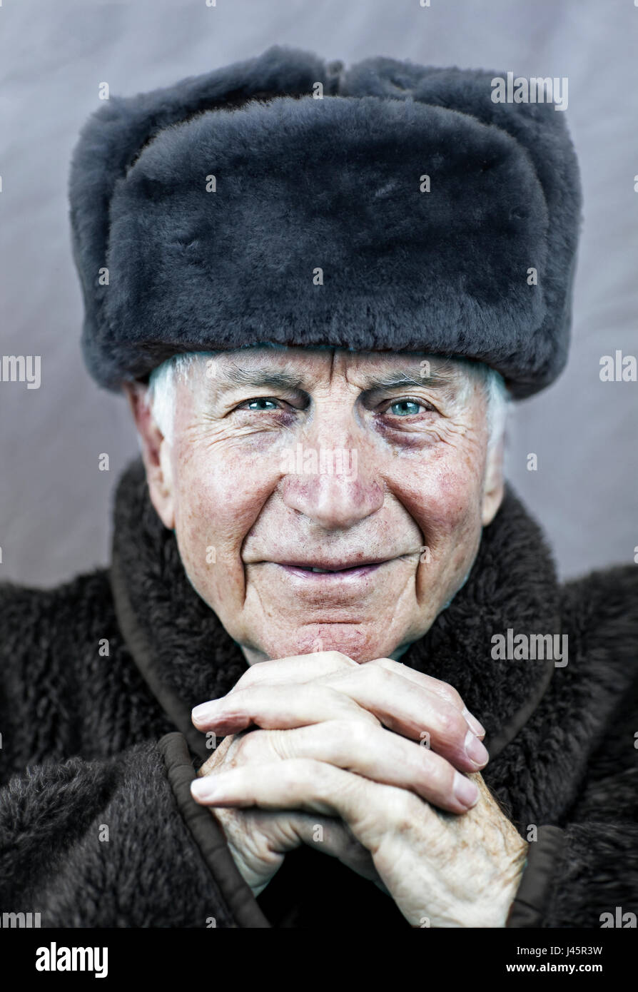 1f5846f1ba2 Old Caucasian man with wrinkled weathered face with vibrant blue eyes  wearing a soviet era Russian military uniform with beaver fur winter hat