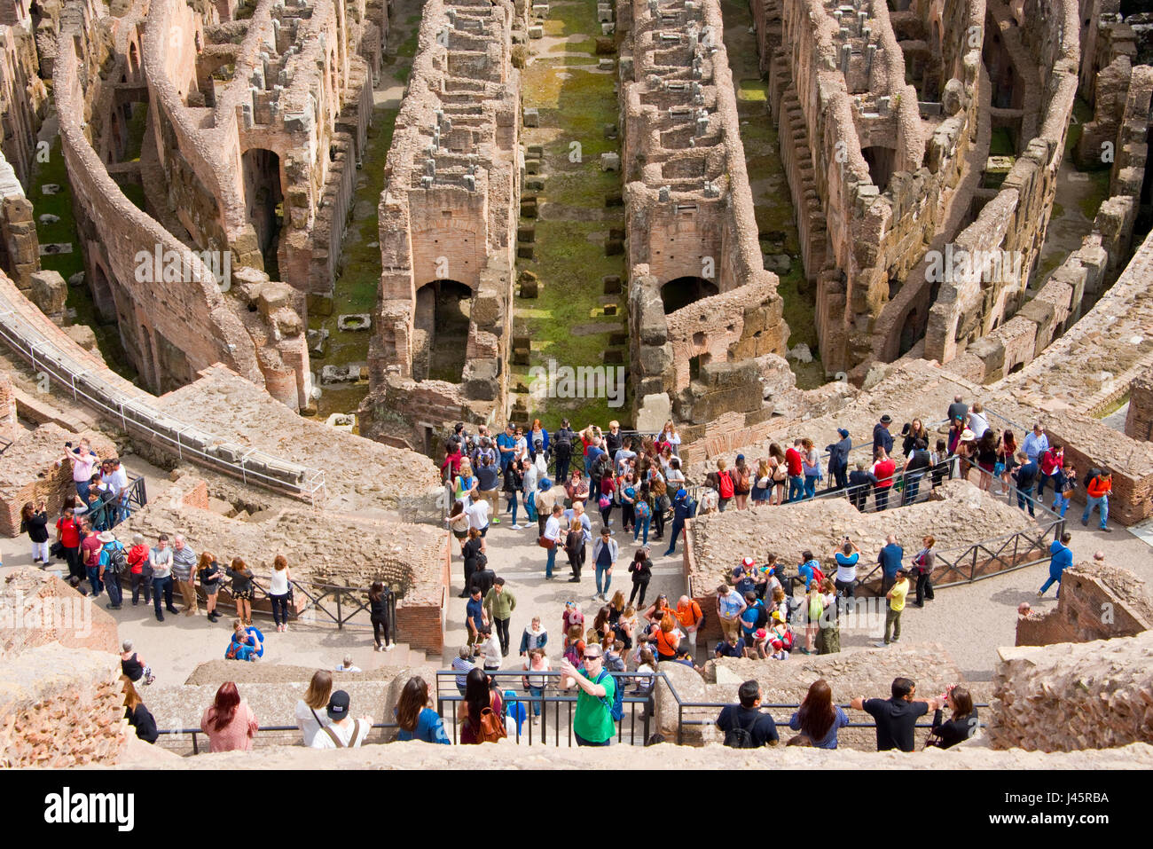 An aerial compressed perspective interior view of the amphitheatre inside the Colosseum with tourists visitors on - Stock Image