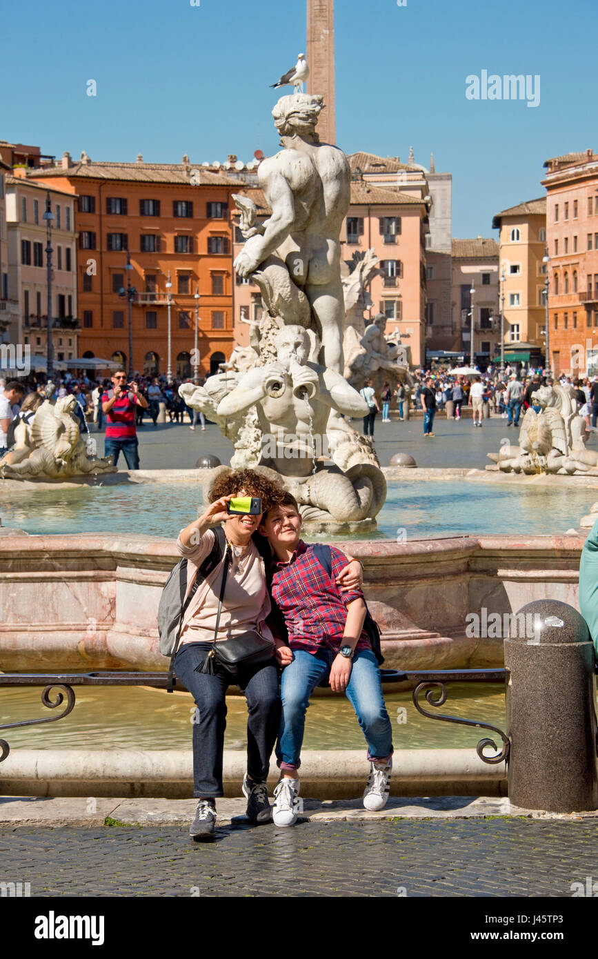 Fontana del Moro or Moor Fountain in Piazza Navona (Rome) with 2 people tourists visitors taking a selfie photograph - Stock Image