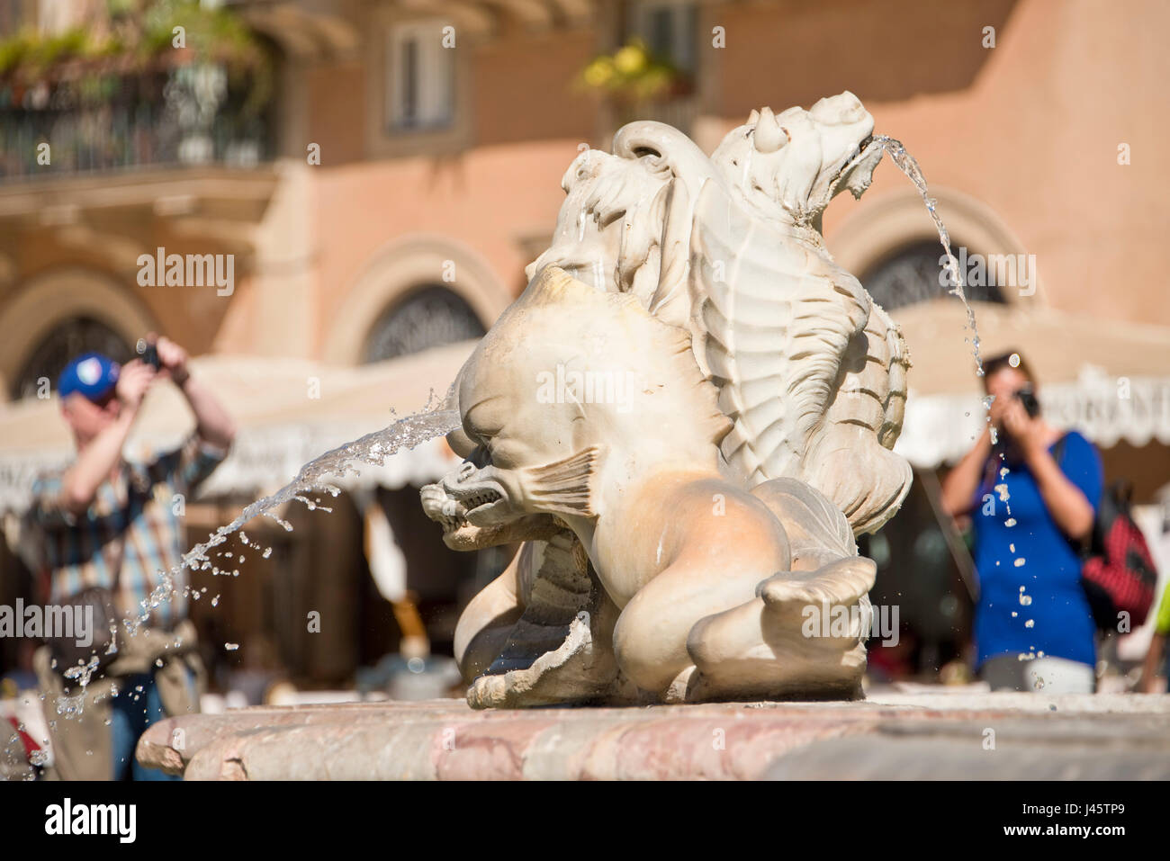 A close up on the Fontana del Moro or Moor Fountain in Piazza Navona with 2 out of focus people tourists visitors - Stock Image