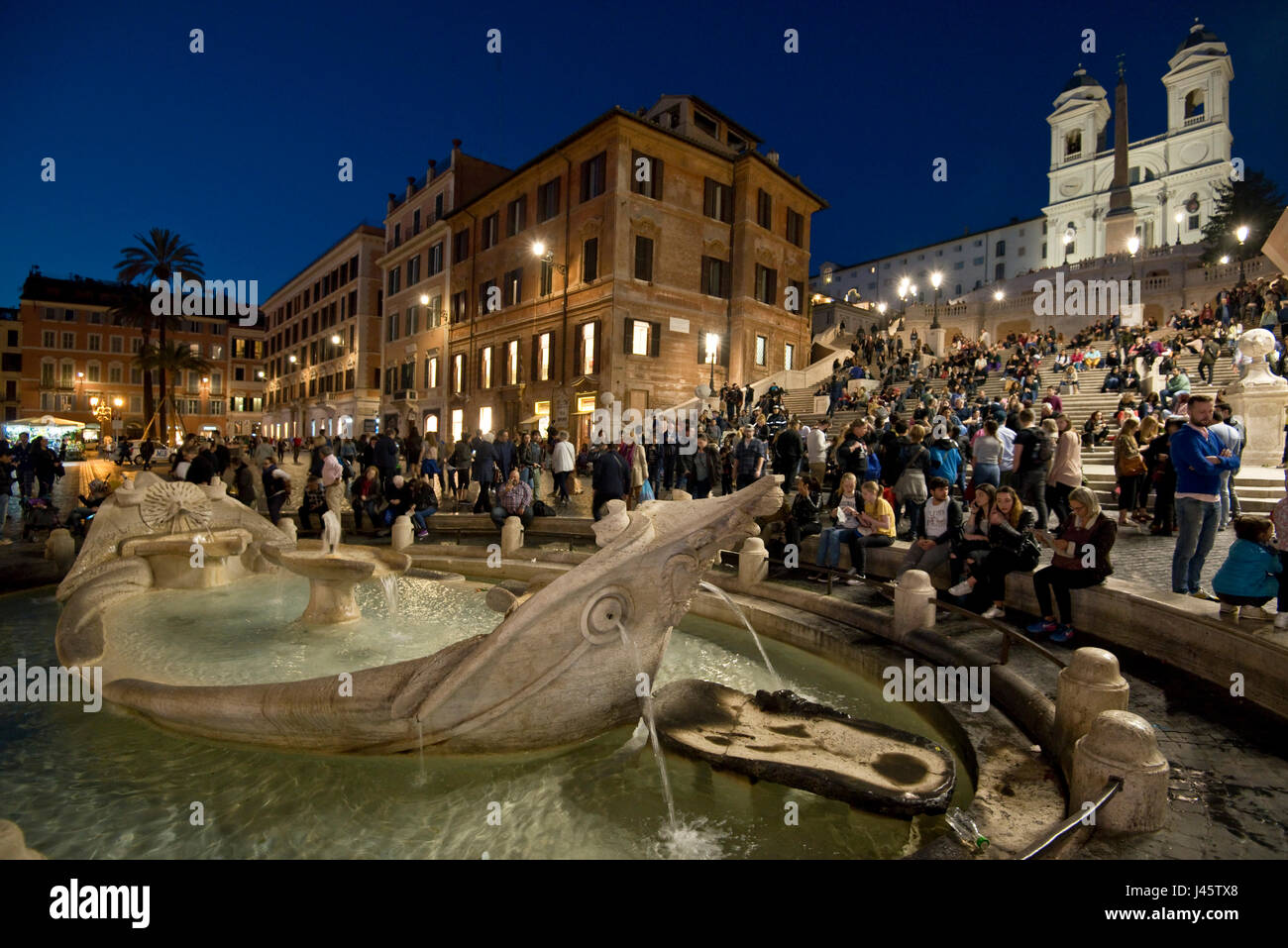 Spanish Steps in Rome with tourists and visitors evening, night with the Trinità dei Monti church background - Stock Image