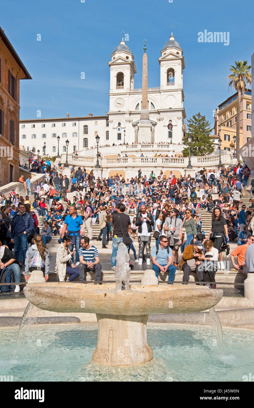 Spanish Steps in Rome with tourists on a sunny day with blue sky Trinità dei Monti church in the background - Stock Image