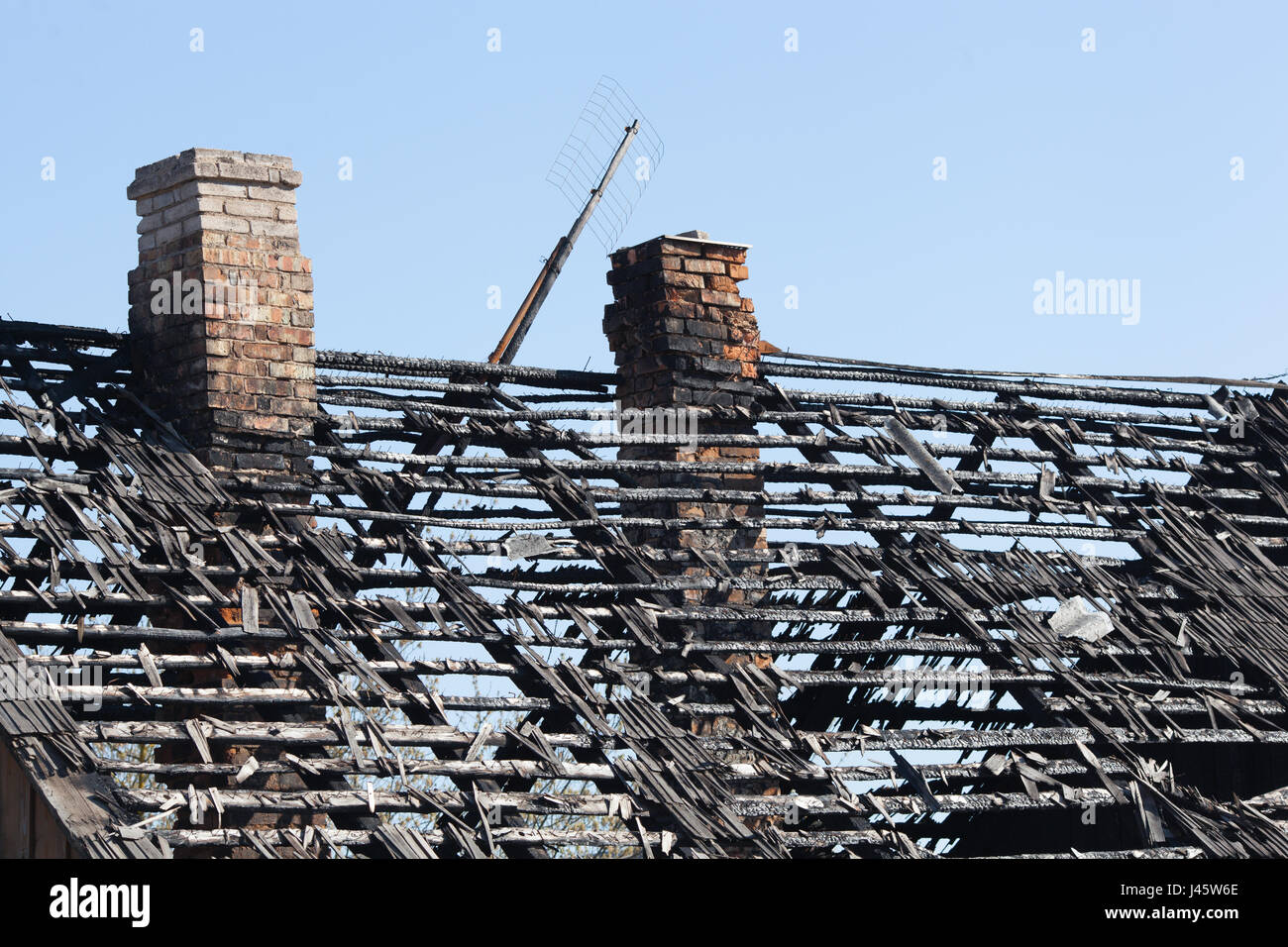 The charred roof and the surviving chimney. - Stock Image