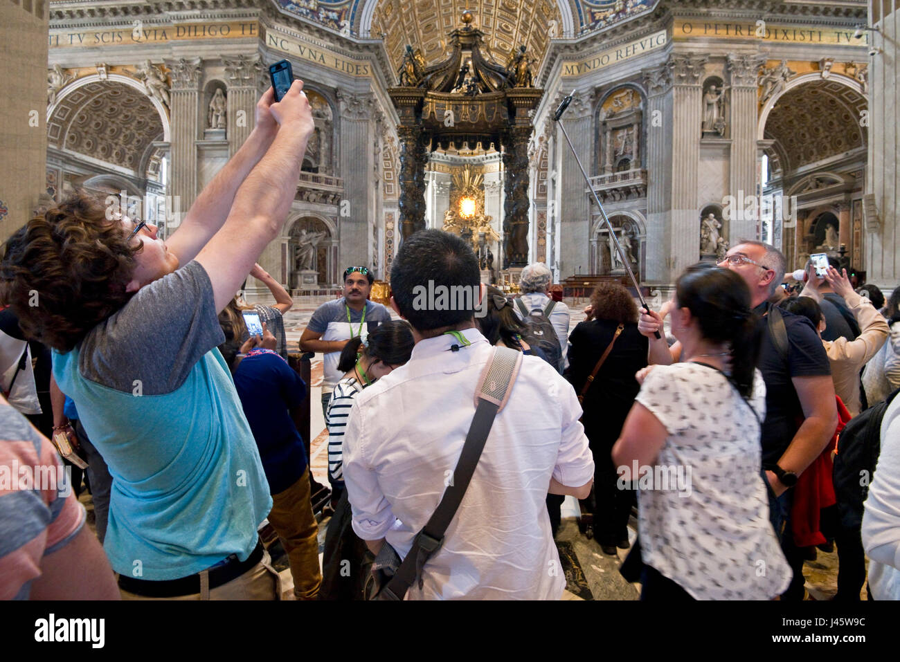 A wide angle interior view inside St Peter's Basilica of the main alter and crowds of tourists and visitors - Stock Image