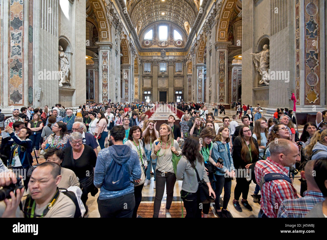 A wide angle interior view inside St Peter's Basilica of the main alter and crowds of tourists and visitors. - Stock Image