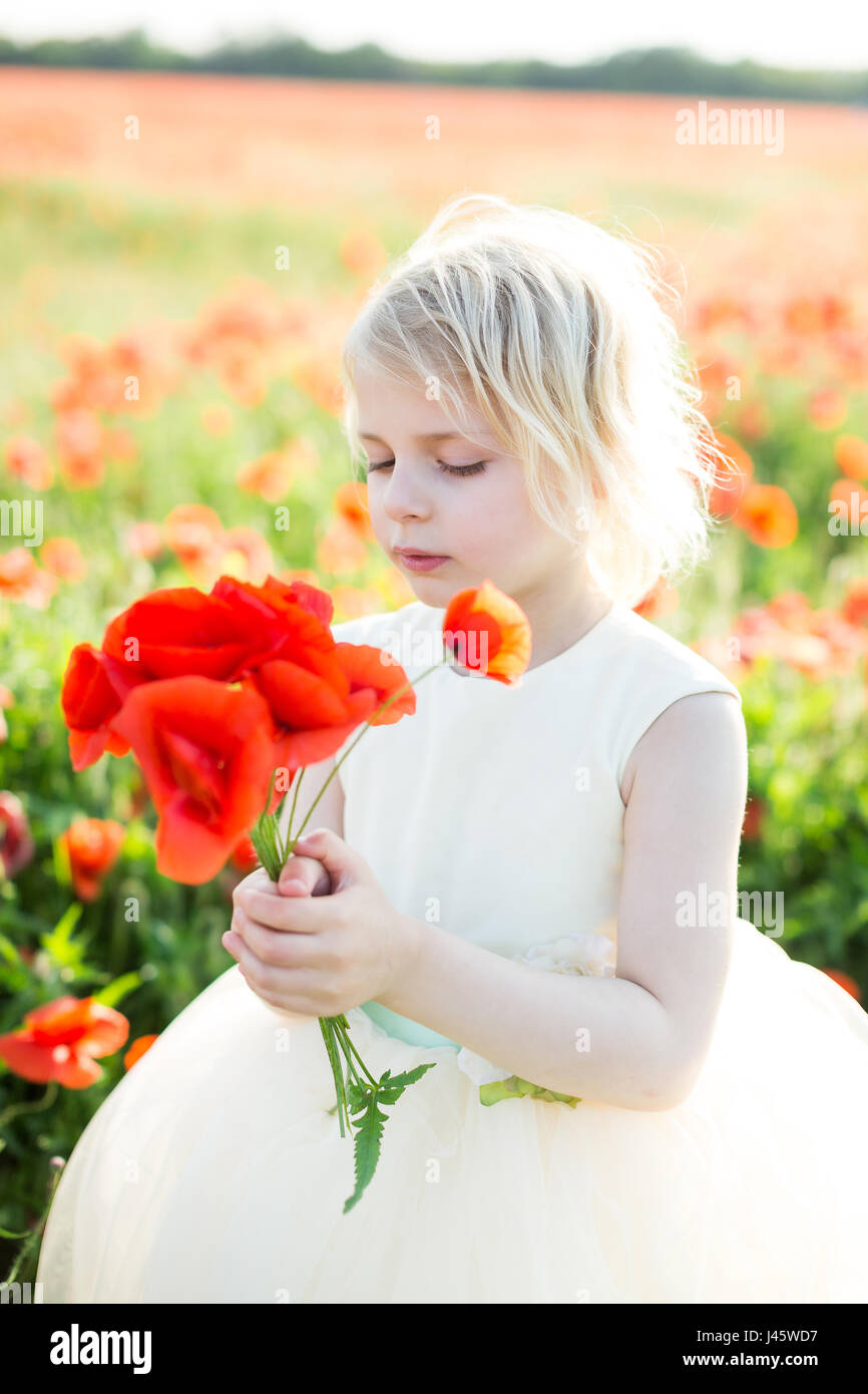 little girl, summer, childhood, childcare, fashion concept - small cute faire-haired princess with bouquet of poppies Stock Photo