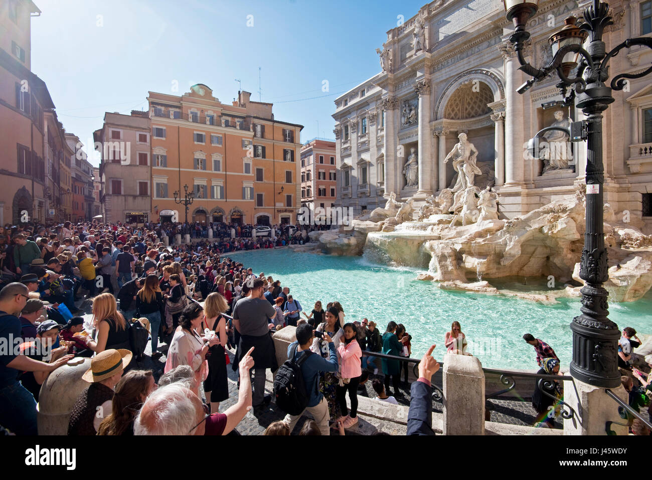 The Trevi Fountain 'Fontana di Trevi' in Rome with crowds of tourists and visitors on a sunny day with blue - Stock Image