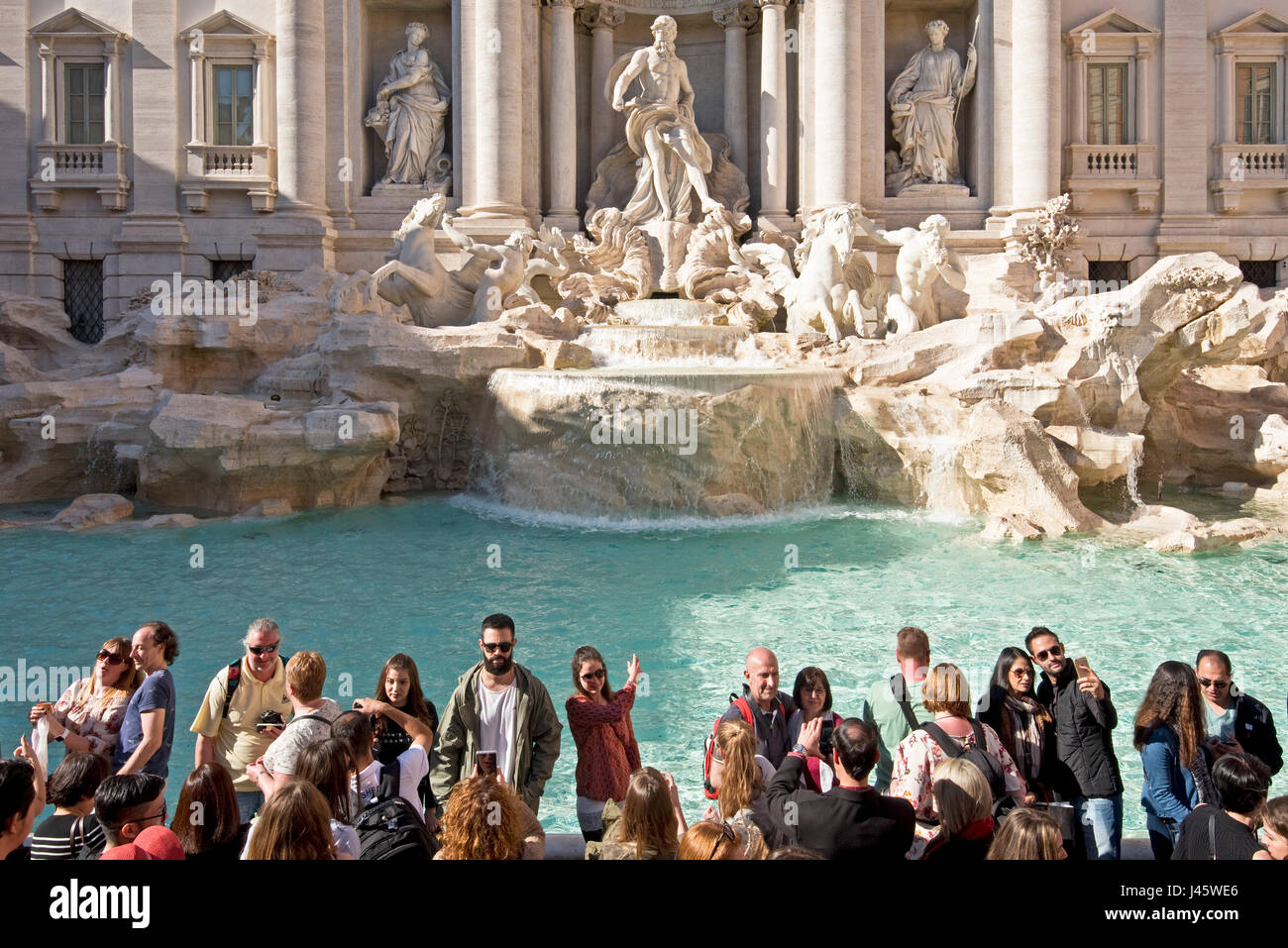"The Trevi Fountain ""Fontana di Trevi"" in Rome with crowds of tourists and visitors on a sunny day with blue sky. Stock Photo"