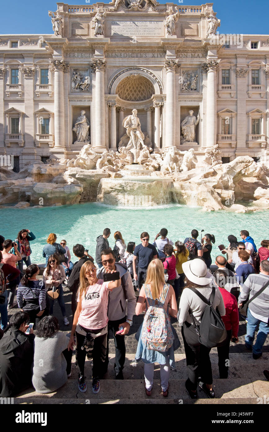 "The Trevi Fountain ""Fontana di Trevi"" in Rome with crowds of tourists and visitors taking photographs, posing and Stock Photo"