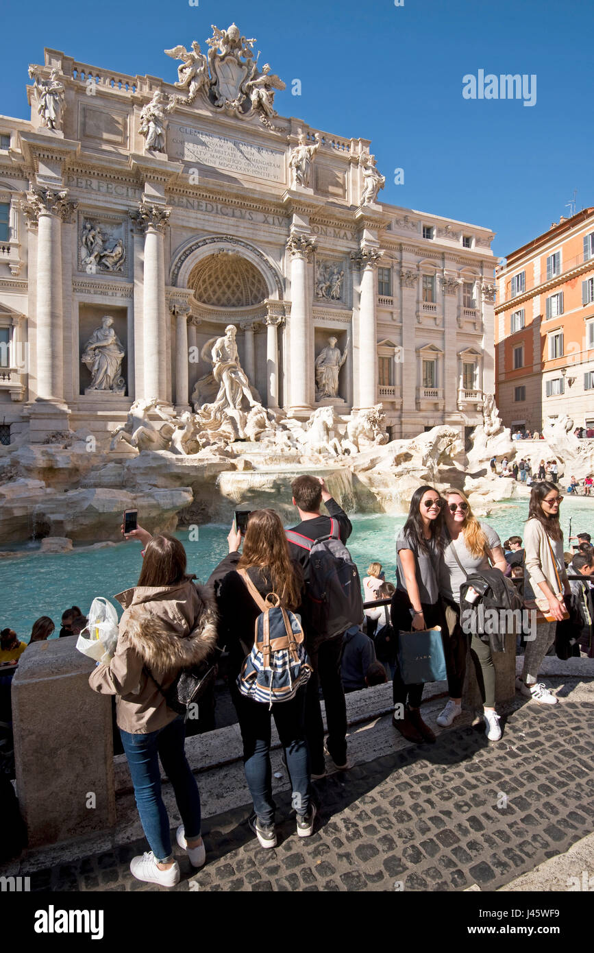 The Trevi Fountain 'Fontana di Trevi' in Rome with crowds of tourists and visitors taking photographs, posing - Stock Image