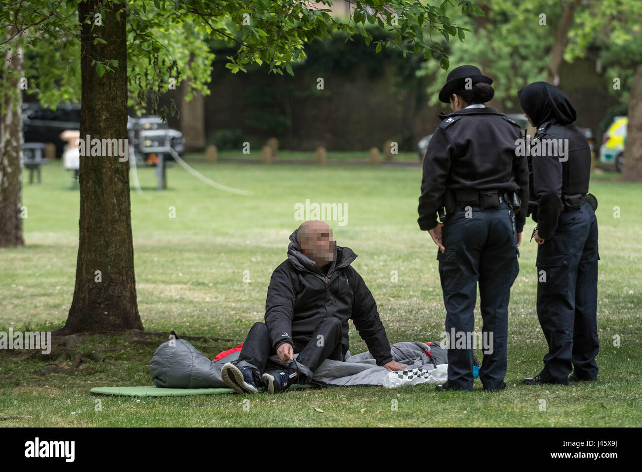 Police officers question then move on a rough sleeper in London's Geraldine Mary Harmsworth Park. UK. - Stock Image