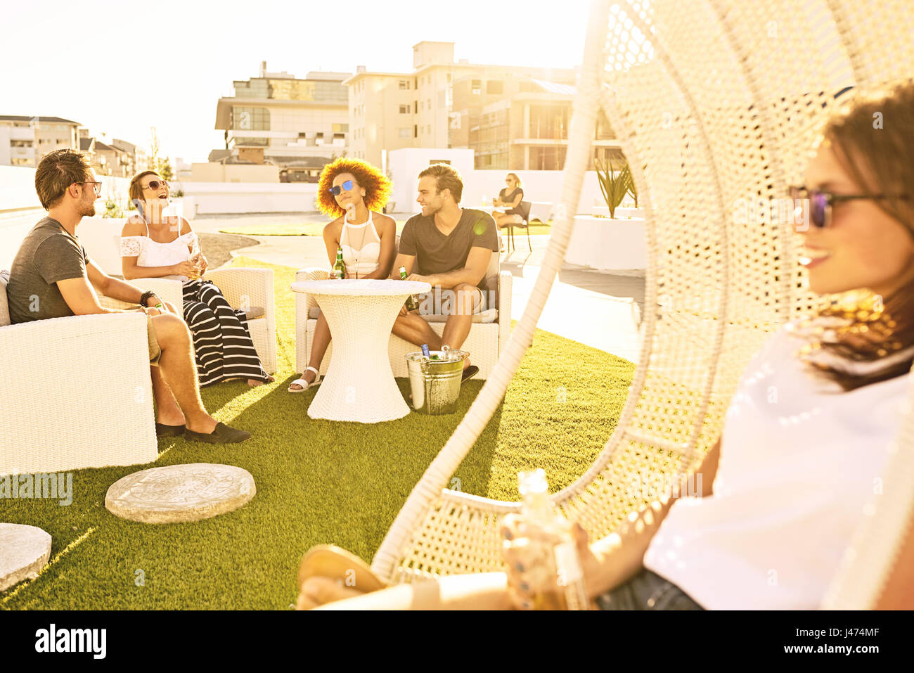 Beautiful young adults socialising together outdoors on an urban rooftop - Stock Image