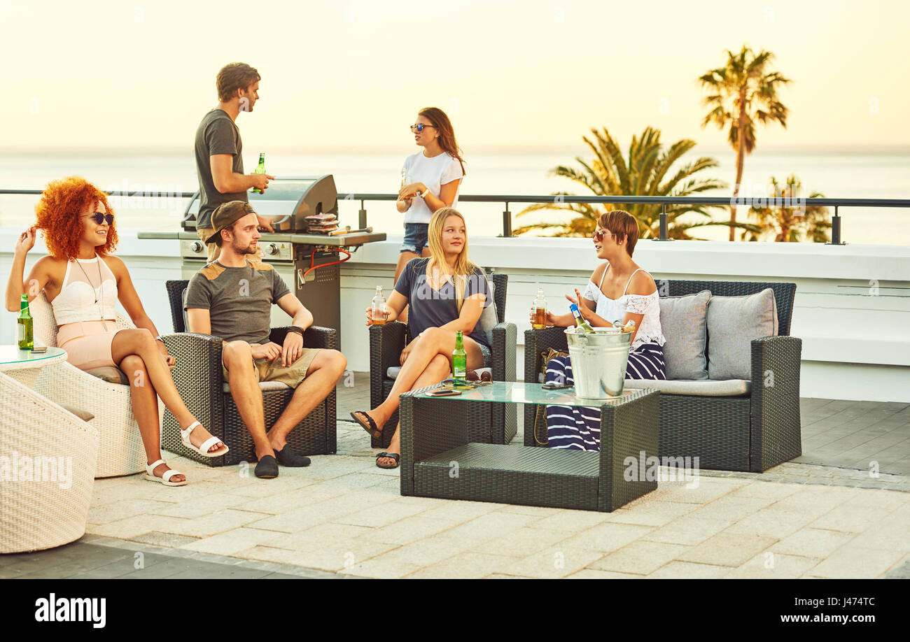 Happy group of close friends socialising together on a rooftop - Stock Image