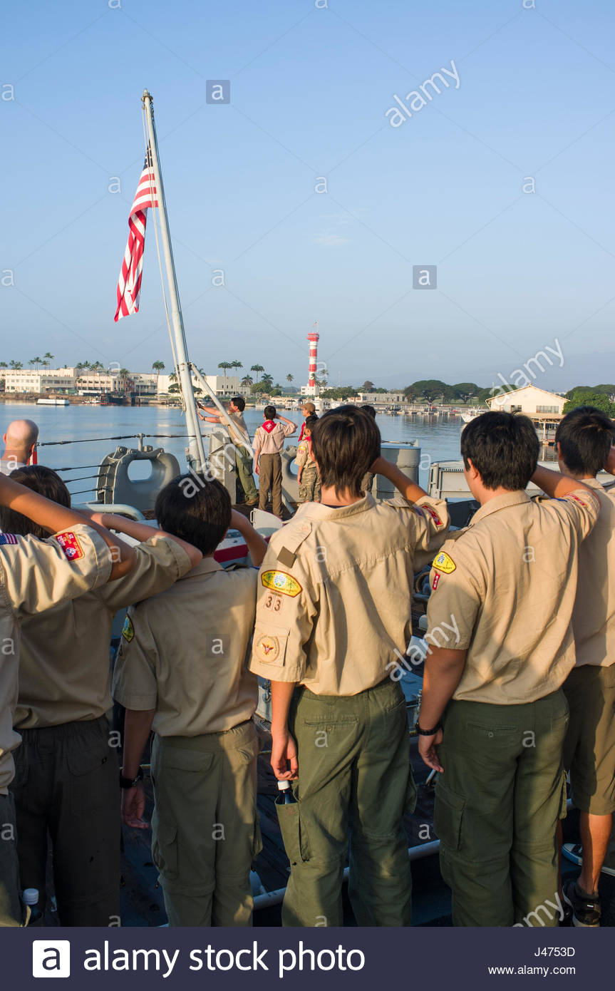 Group of Boy Scouts standing at attention and saluting as the flag of the United States of America is raised aboard - Stock Image