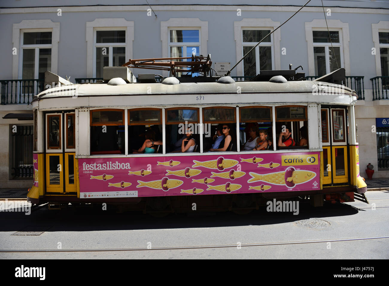 Tourist traveling on the famous tram 28 in Lisbon, Portugal. - Stock Image